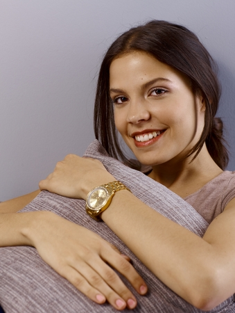 Portrait of attractive young woman smiling happy, looking at camera, hugging pillow. photo