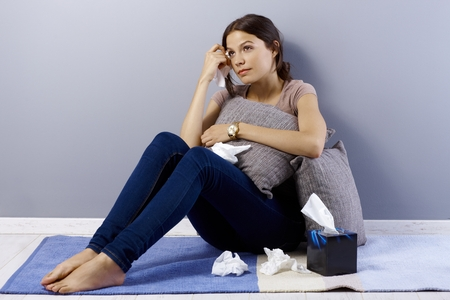Heart-broken young woman sitting on floor at home, crying, wiping away tears by hanky. Stock Photo - 29562368