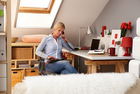 Young blonde woman working at home, using tablet, talking on phone. photo