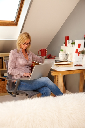 alone person: Blonde woman browsing internet on laptop computer at home, sitting in study. Stock Photo