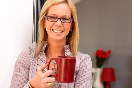 Closeup portrait of happy blonde woman holding tea mug, smiling, looking at camera. photo
