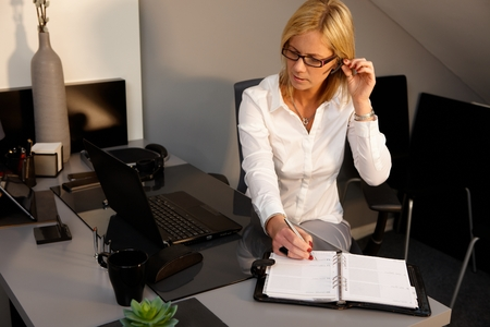 Blonde woman sitting at desk, working in office, talking on phone, writing notes. photo