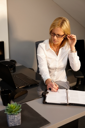 Blonde businesswoman sitting at desk, writing notes to personal organizer, using earbuds. photo