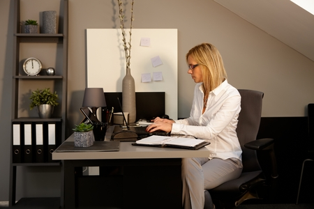 view of an elegant office: Young woman sitting at desk in office, working with laptop computer, typing on keyboard.