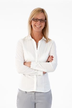 Confident blonde businesswoman smiling arms crossed, standing over white background. photo