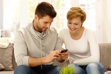 Young couple sitting on sofa at home, using mobilephone, smiling. photo