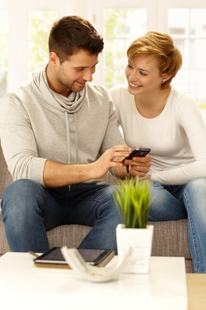 calling on phone: Happy couple sitting on sofa at home, using mobilephone, smiling. Stock Photo