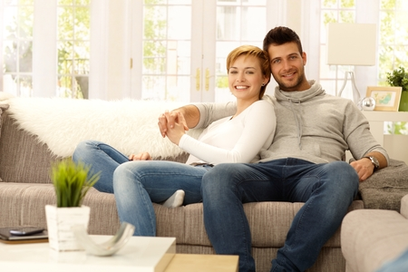Portrait of attractive young couple sitting on sofa at home, hugging, looking at camera, smiling. Stock Photo