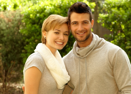 gingerish: Happy young loving couple smiling outdoors, looking at camera. Stock Photo