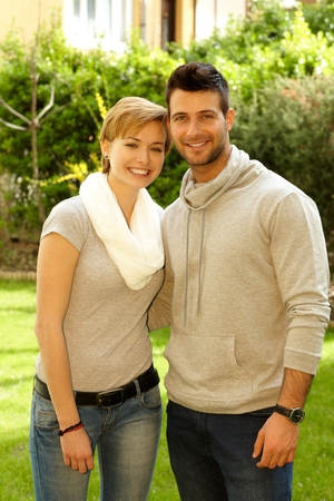 Young loving couple hugging and smiling outdoors, looking at camera. photo