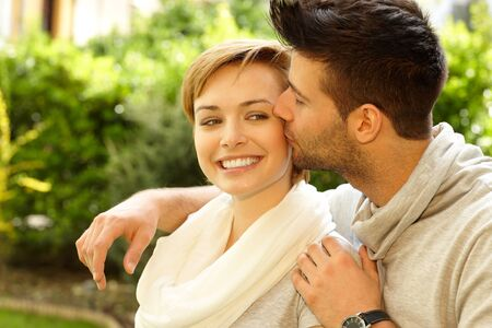 Closeup photo of happy young couple. Man kissing girlfriend.