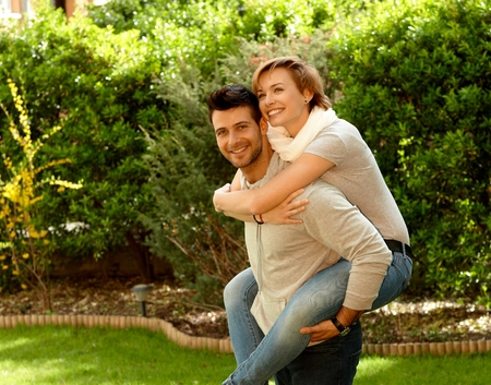 Young couple in the green. Man carrying girlfriend, having fun together, laughing. photo