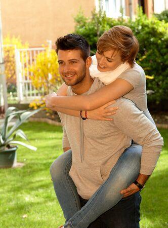 gingerish: Man giving piggyback ride to girlfriend outdoors, smiling.
