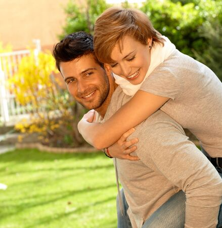 carrying girlfriend: Young couple having fun outdoors. Man carrying girlfriend on his back, both smiling.