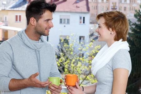 Young couple drinking coffee at the terrace, talking, smiling. photo