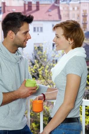 Young loving couple having coffee at the balcony, smiling. Side view. photo