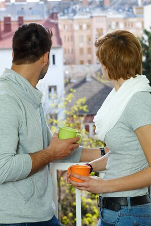 Young couple searching distance, standing at the balcony. photo