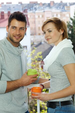 Attractive young couple having coffee at the balcony, looking away. photo