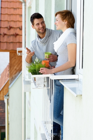 Young couple standing at balcony, having coffee, chatting, smiling. photo