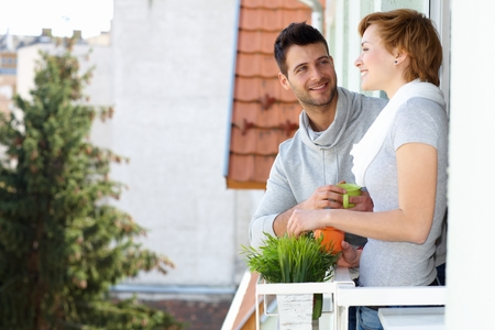 Happy young couple standing at balcony, smiling, having coffee. photo
