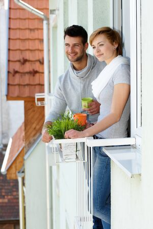 Happy young couple standing at balcony, smiling, looking away. photo
