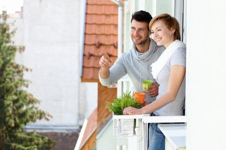 検索距離、バルコニーで幸せな若いカップルの立っている笑顔。