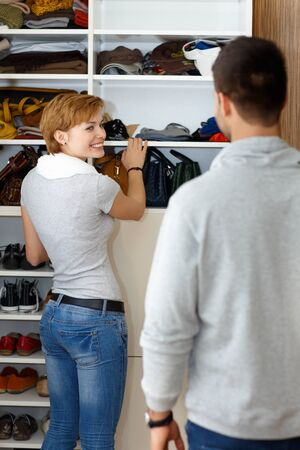 Young woman packing in walk-in closet, smiling to husband. photo