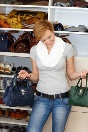 dudando: Mujer joven delante del armario abierto de pie, dudando que la bolsa para llevar. Foto de archivo