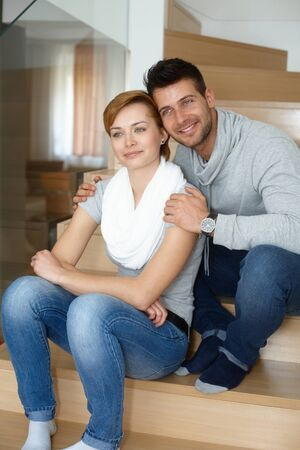 Young loving couple sitting at home in stairway, smiling, looking away heads together. photo