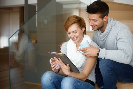gingerish: Happy young couple using tablet computer at home, smiling. Stock Photo