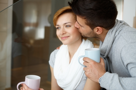 be kissed: Happy young couple kissing at home, smiling.