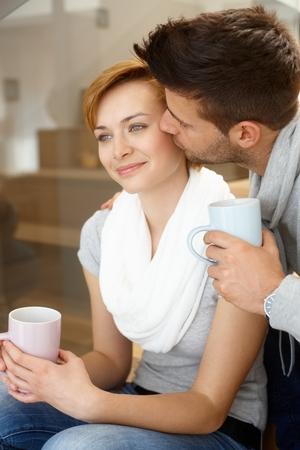 be kissed: Felice giovane coppia baciare in scala, sorridendo.