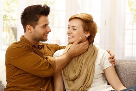 hombre sentado: Pareja joven abrazando en casa, sonriendo. Foto de archivo
