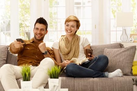 pareja viendo television: Feliz pareja de jóvenes viendo la televisión en casa. Foto de archivo
