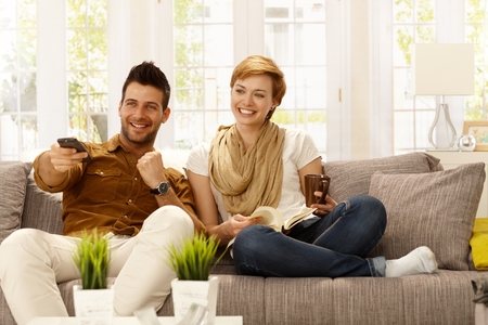 enjoy space: Happy young couple watching tv at home.