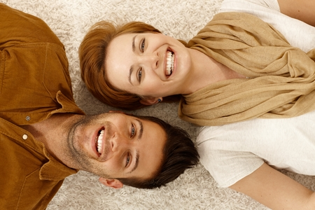 gingerish: Attractive young couple lying on carpet, looking at camera, smiling happy. Above view.