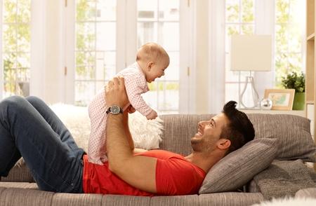 bebes: Padre feliz acostado en el sofá, sosteniendo la niña, jugando, sonriendo. Vista lateral.