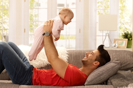 Happy young father lying on sofa, lifting baby girl high up, smiling, having fun. Side view. photo