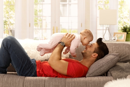 red sofa: Young father playing with baby daughter as lying on sofa at home, smiling happy having fun. Side view.