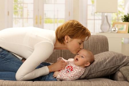Madre joven que besa al bebé, jugando en el sofá.