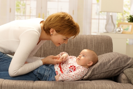 Happy young mother caressing baby girl on sofa, smiling. photo