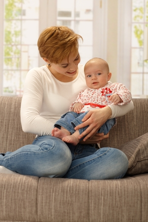 gingerish: Happy young mother holding baby girl in arms, sitting on sofa.