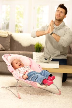 familia orando: Padre joven orando por la paz a través del llanto del bebé.