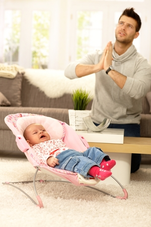 whining: Young father praying for peace by crying baby. Stock Photo