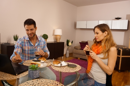 Young couple having breakfast on holiday in apartment. photo