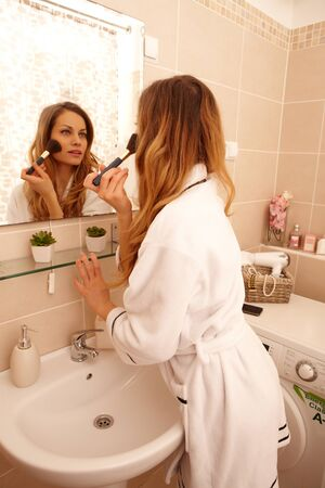 putting in: Attractive young woman putting on makeup in the morning using mirror.