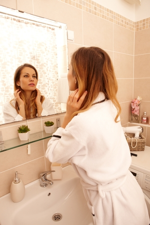 Young woman watching her face in mirror in the morning in dressing gown.
