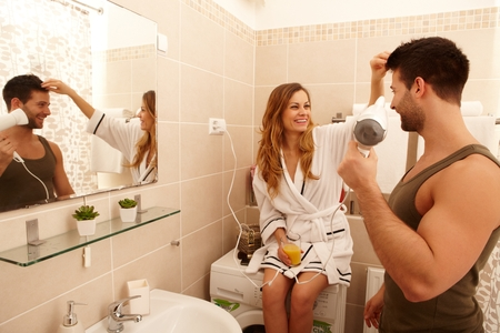 Young couple getting ready in the bathroom in the morning, drying hair, drinking orange juice.