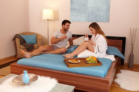 Young loving couple having breakfast in the morning in bed. photo