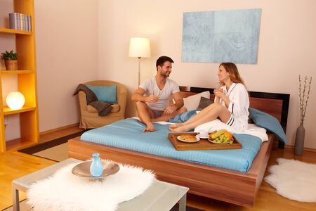 Happy young couple having breakfast in bed, having fun. photo